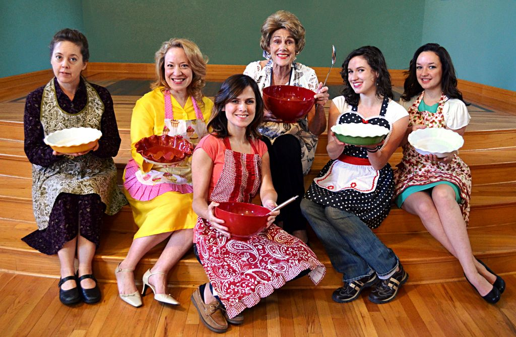 The six Righteous Housewives of Utah County in their aprons, ready to cook up a meal. Left to right: Holly Fowers, April Fossen, Anne Cullimore Decker, Anne Louise Brings, Haley McCormick, and Nicki Nixon on the front row. Photo by Morgan Donavan, courtesy of AP Productions.