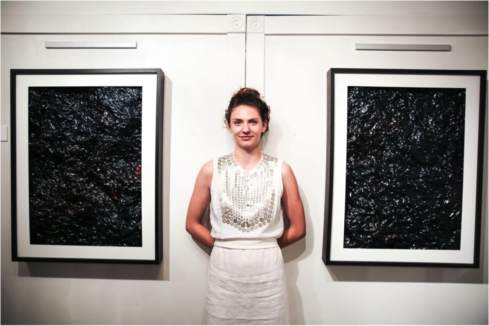Ali Mitchell at her exhibit Oil Fields. Photo by Blake Peterson.