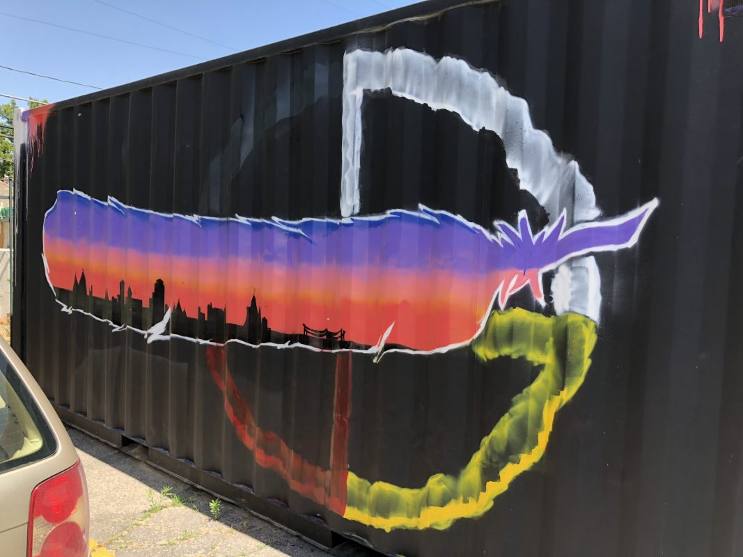 Spray paint mural featuring Salt Lake City skyline in the form of a feather.