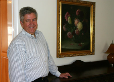Tom Alder, in his Salt Lake City home, stands in front of a painting by Lewis Ramsey he received from his mother along with the story of a stolen wedding ring.